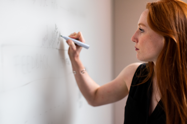 Female IT project manager writing on a whiteboard
