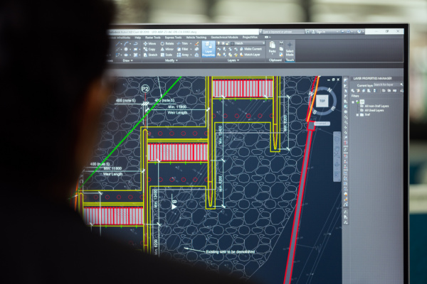 Female engineer using AutoCAD to plan a dam