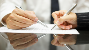 Two hands signing business documents
