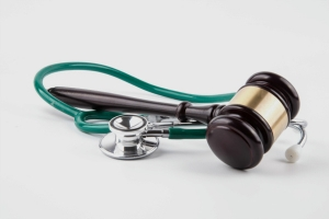 Stethoscope and gavel sitting on a white table
