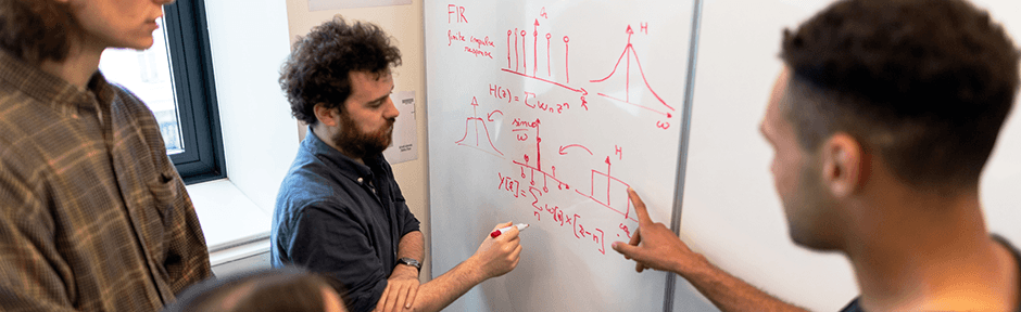Group of engineers working at a whiteboard