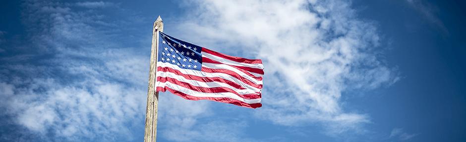 American flag flying against a bright blue sky
