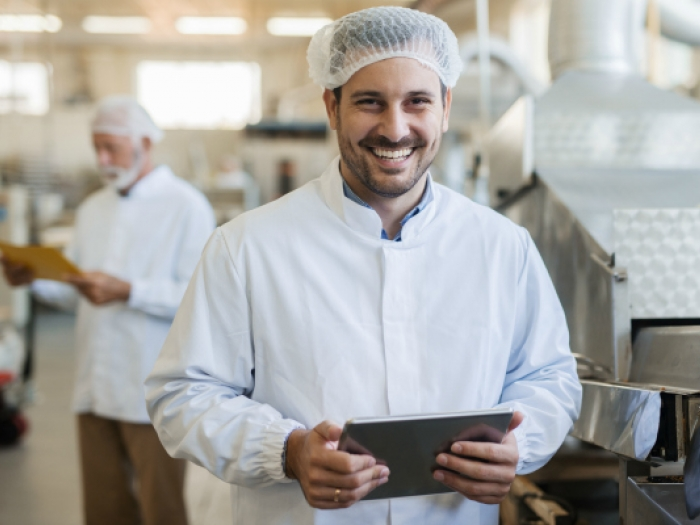 Smiling man in a food factory